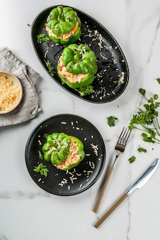 秋のレシピ。ミンチ肉、ニンジン、トマト、ハーブ、チーズを詰めた自家製ピーマン。白い大理石のテーブル、ポーションプレート、ナイフとフォーク、コピースペーストップビュー