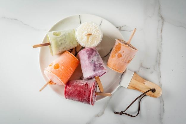 健康的な夏のデザート。アイスクリームアイスキャンディー。冷凍トロピカルジュース、スムージーブルーベリー。スグリ、オレンジ、マンゴー、キウイ、バナナ、ココナッツ、ラズベリー。白い大理石のテーブル、プレートコピースペーストップビュー