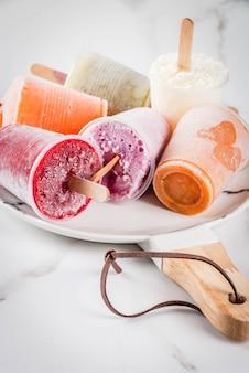 Здоровые летние десерты. фруктовое мороженое. замороженные тропические соки, смузи черника. смородина, апельсин, манго, киви, банан, кокос, малина. на белом мраморном столе табличка с копией пространства