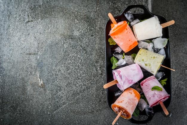 Здоровые летние десерты. фруктовое мороженое. замороженные тропические соки, смузи черника. смородина, апельсин, манго, киви, банан, кокос, малина. на черном каменном столе, тарелка копия пространства вид сверху