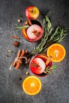 伝統的な冬と秋の飲み物。クリスマスと感謝祭のカクテル。オレンジ、リンゴ、ローズマリー、シナモン、スパイスのホットワイン