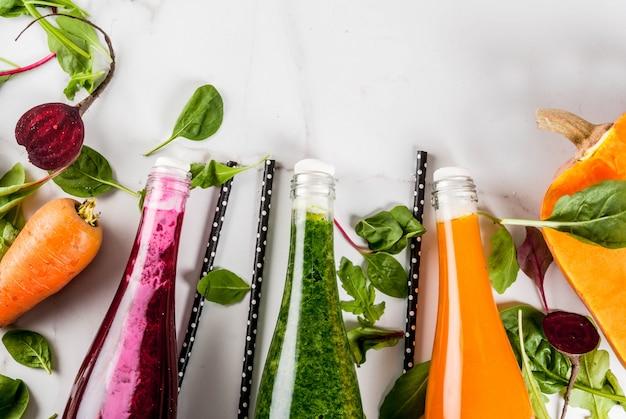 ビーガンダイエット食品。カラフルな新鮮な有機スムージーの選択は、秋野菜と一緒に飲みます:ビートルート、カボチャ、ニンジン、葉物野菜。ボトル、白いテーブル。コピースペーストップビュー