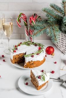 ローズマリーとクランベリーで飾られたクリスマスフルーツケーキまたはプリン、クリスマスの装飾、白い大理石のテーブルの上、