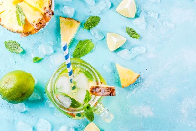 Тропический напиток, ананасовый мохито или лимонад со свежим лаймом и мятой светло-голубой, вид сверху