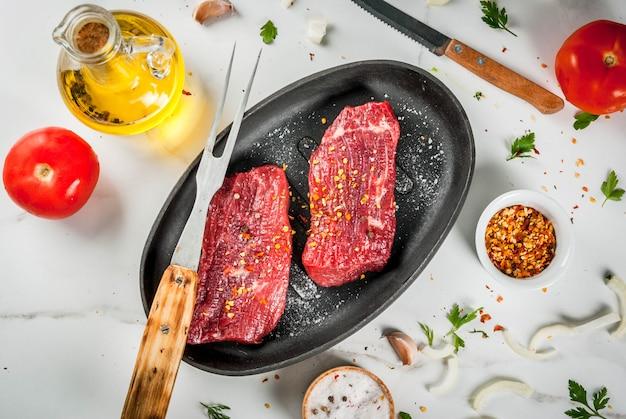 肉、牛肉。フライパンで新鮮な生ステーキ。スパイス(塩、コショウ)、新鮮な野菜のトマト、ニンジン、ニンニク、玉ねぎ。肉用のフォークとナイフを備えた白い大理石のテーブルの上。上面図