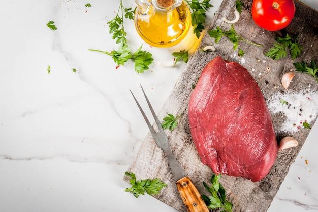 牛フィレ肉のテンダーロインを調理します。肉、スパイス(塩、コショウ、パセリ、ニンニク、玉ねぎ、トマト)のフォークと古いまな板の上の仔牛の切り身の大きな全体。上面図