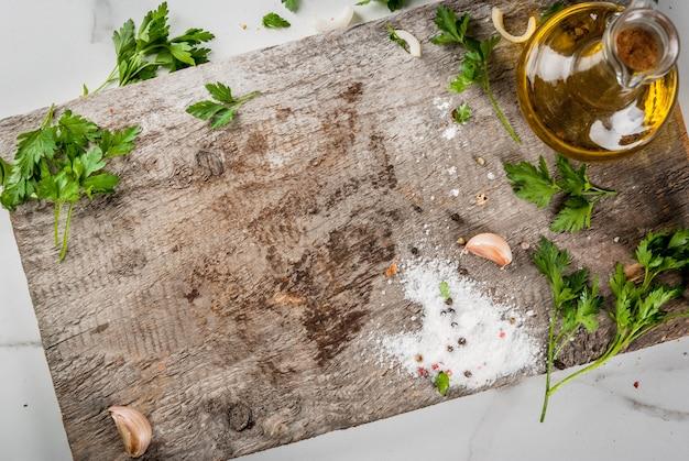 Приготовление пищи. старая разделочная доска на белом мраморном кухонном столе. оливковое масло, нож, специи, соль, перец, чеснок, петрушка. вид сверху