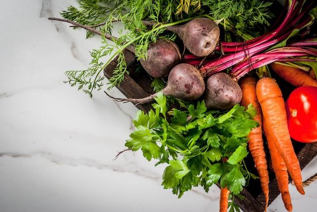Лето, осенний урожай. свежие органические овощи фермы в деревянном ящике на белой мраморной столовой свекле, моркови, петрушке, помидорах. вид сверху