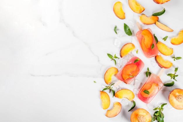 夏のデザート。冷凍ドリンク。ミントと冷凍桃茶から甘いフルーツアイスキャンディー。桃、ミント、氷を材料にした白い大理石のテーブルの上。上面図