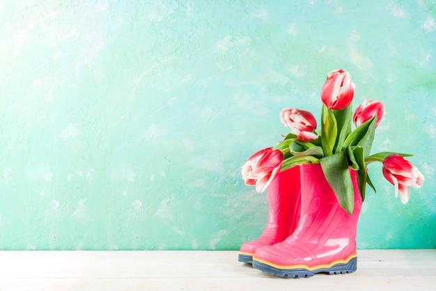 春 。明るい青と木製の白のゴム製の明るいピンクのブーツの花チューリップ。