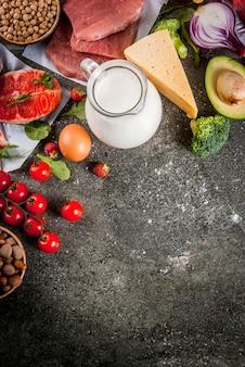 健康的な食事の背景。有機食材、スーパーフード:牛肉と豚肉、鶏肉の切り身、サケ、魚、豆、ナッツ、牛乳、卵、果物、野菜。黒い石のテーブル、コピースペース平面図