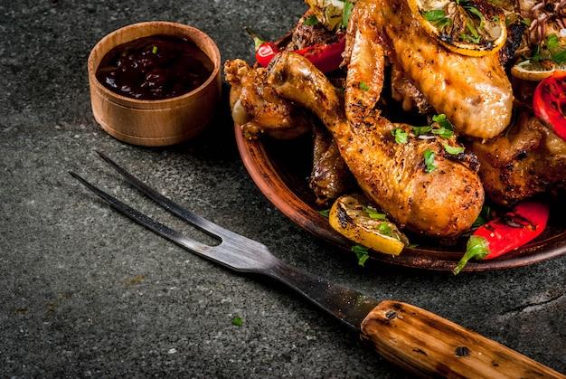 夏の食べ物。バーベキュー、グリルパーティーのアイデア。鶏の足、手羽先のグリル、火で揚げた。唐辛子、レモン、バーベキューソース。黒いプレート上の暗い石のテーブルコピースペース