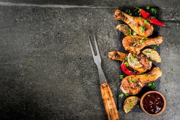 夏の食べ物。バーベキュー、グリルパーティーのアイデア。鶏の足、手羽先のグリル、火で揚げた。唐辛子、レモン、バーベキューソース。暗い石のテーブル。コピースペーストップビュー