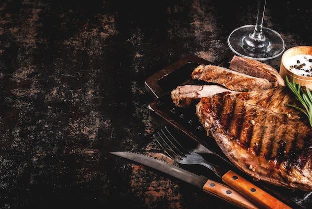 グリル鍋ボードにスパイスと牛肉のグリルステーキ、赤ワイングラス。