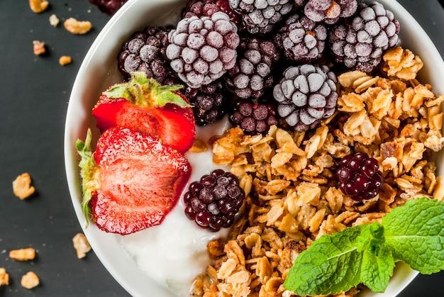Здоровый завтрак. летние ягоды и фрукты. домашний греческий йогурт с мюсли, ежевикой, клубникой и мятой. стол из черного камня, с ингредиентами. вид сверху