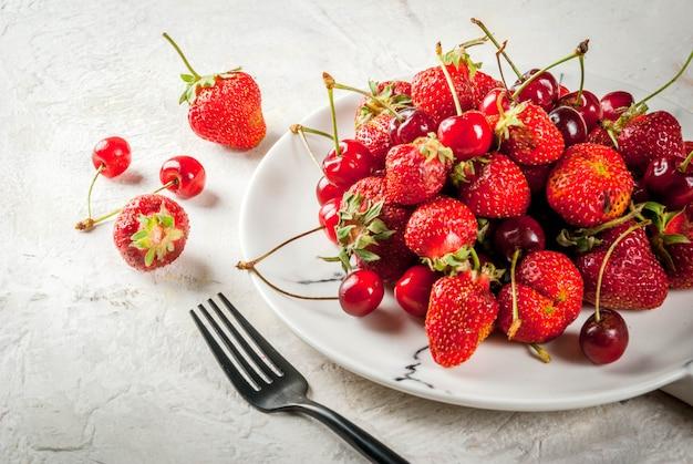 健康的な朝食、ランチ、スナック。夏の果実と果物。有機の新鮮なチェリーとイチゴは、白いテーブルの上に白い大理石のプレートをラウンドします。