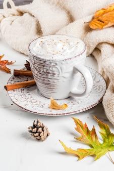 Осенние горячие напитки. тыквенный латте со взбитыми сливками, корицей и анисом на белом мраморном столе, со свитером, осенними листьями и еловыми шишками.