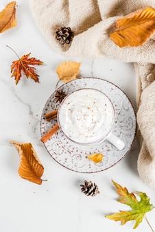 Осенние горячие напитки. тыквенный латте со взбитыми сливками, корицей и анисом на белом мраморном столе, со свитером, осенними листьями и еловыми шишками. вид сверху