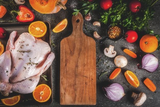 Готовим ужин на рождество, день благодарения. традиционными осенними ингредиентами являются овощи, тыква, грибы, курица или индейка, зелень, специи. темный стол, вид сверху