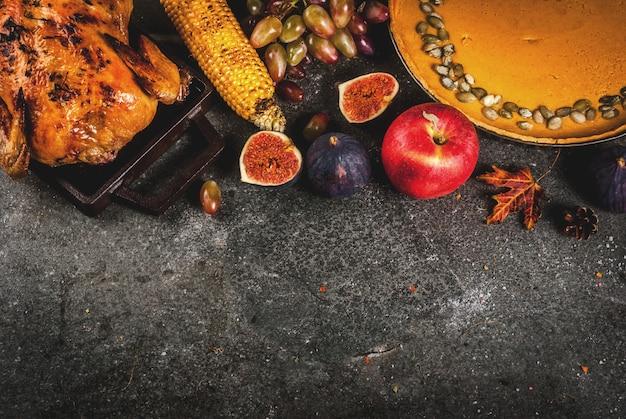感謝祭の食べ物。ローストチキンまたは七面鳥の丸焼き、秋野菜と果物:トウモロコシ、カボチャ、パンプキンパイ、イチジク、リンゴ、ダークグレー、トップビュー