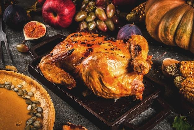 感謝祭の食べ物。ローストチキンまたは七面鳥の丸焼き、秋野菜と果物:コーン、カボチャ、パンプキンパイ、イチジク、リンゴ、ダークグレー、