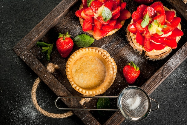 夏と春のデザート。ホームパイは、ミントと粉砂糖で飾られたカスタードとイチゴのタルトをパイします。素朴な黒い石のテーブル、木の板、トレイ。上面図
