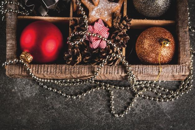 Рождество, новогодние праздничные украшения. елочные шары, гирлянда, пряничные звезды, печенье, формы, бантики для подарков, еловые шишки в деревянной коробке на черном каменном столе, вид сверху