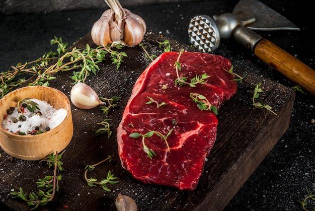 Свежее сырое мясо. говядина. кусок говяжьей вырезки, с топором для нарезки и измельчения мяса, специями готовили тимьян, перец, соль, чеснок. на старой деревянной доске на каменном черном столе.