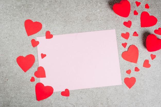 Романтика, день святого валентина. стол из серого камня с чистым листом бумаги для письма или поздравления, украшенный бумажными и плюшевыми красными сердечками, вид сверху