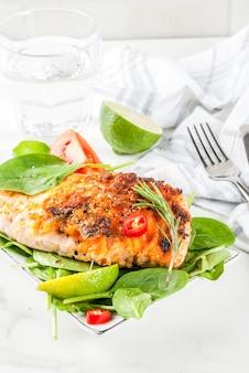 Стейк из лосося на гриле со свежими овощами, шпинатом и лаймом, белый мраморный стол