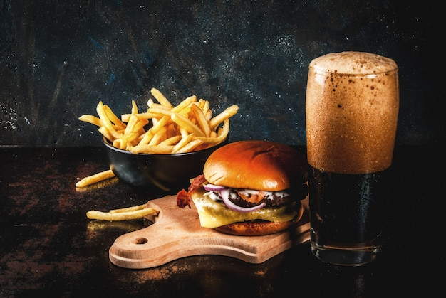 フライドポテトとダークジンジャービールのグラスと新鮮な肉とチーズのハンバーガー
