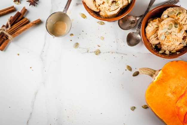 秋のデザートのアイデア、カボチャのレシピ。メープルシロップ、カボチャの種、シナモンとアニスの星、白い大理石のテーブルとセラミックボウルのパンプキンパイアイスクリームジェラート。コピースペーストップビュー