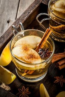 秋と冬の飲み物。伝統的な自家製アップルサイダー、シナモンとアニスの香り豊かなサイダーのカクテル。古い木製の素朴なテーブル、トレイの上。コピースペース
