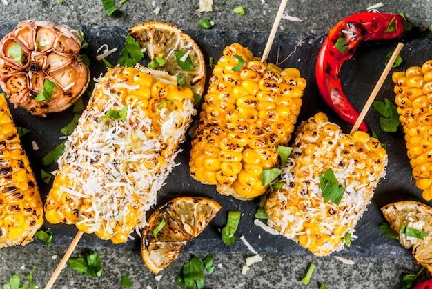 Летняя еда. идеи для барбекю и гриль вечеринок. жареная кукуруза на гриле в огне. с посыпать сыром (мексиканский элот), острым перцем чили и лимоном. на темном каменном столе. топ закрыть вид