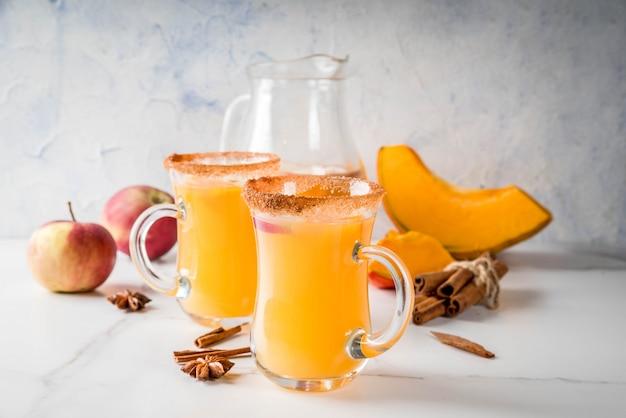 ハロウィーン、感謝祭。伝統的な秋、冬の飲み物とカクテル。スパイシーなホットパンプキンサングリア、リンゴ、シナモン、アニス入り。