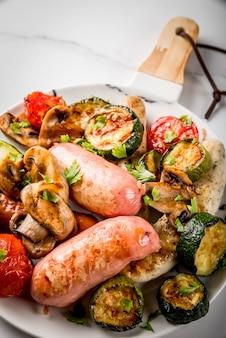 バーベキュー。野菜バーベキューきのこ、トマト、ズッキーニ、タマネギとさまざまな肉のグリルソーセージの品揃え。白い大理石のテーブルの上、皿の上、ソース付き。ビューを閉じる