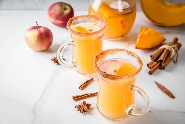 ハロウィーン、感謝祭。伝統的な秋、冬の飲み物とカクテル。スパイシーなホットパンプキンサングリア、リンゴ、シナモン、アニス入り。ガラスのマグカップで、白い大理石のテーブルの上。セレクティブフォーカス、コピースペース