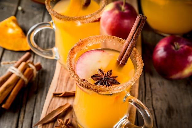ハロウィーン、感謝祭。伝統的な秋、冬の飲み物とカクテル。スパイシーなホットパンプキンサングリア、リンゴ、シナモン、アニス入り。ガラスのマグカップで、古い素朴な木製のテーブル。セレクティブフォーカスコピースペース