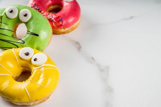 子供向けのアイデアは、ハロウィーンで扱います。目、緑、黄色、赤いチョコレートシュガーアイシングとモンスターの形のカラフルなドーナツ。白い大理石のテーブルの上。コピースペース
