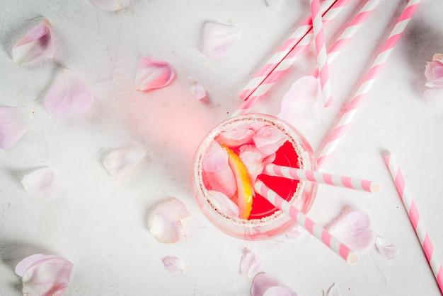 Летние прохладительные напитки. коктейль светло-розовой розы, с розовым вином, лепестками чайной розы, лимоном. на белом каменном бетонном столе. с полосатыми розовыми трубочками, лепестками и розовыми цветами. вид сверху