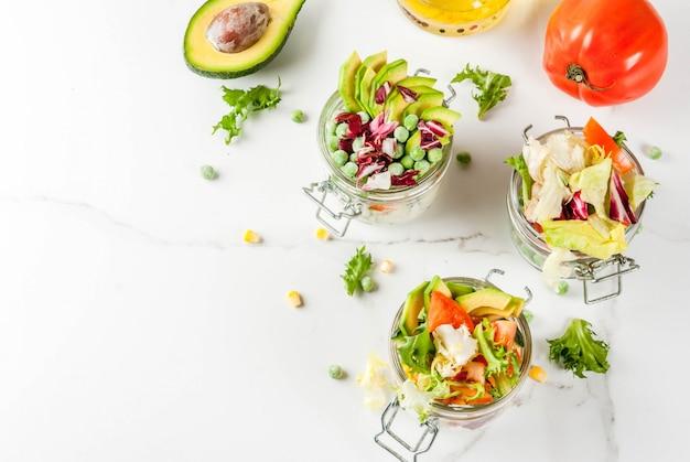 白い大理石のテーブルの上の新鮮な野菜と健康的なドレッシングの瓶に新鮮なサラダ、