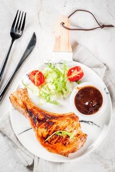 健康食品。トマト、ルッコラ、レタスの葉、キャベツ、グリルしたポークまたは仔牛の骨付きカツレツのフレッシュサラダの一部、バーベキューソース。白い大理石のプレート、白いテーブルの上。上面図