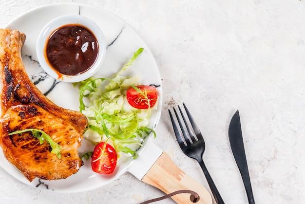 Здоровая пища. порция свежего салата с помидорами, рукколой, листьями салата, капустой и жареной свининой или телятиной на косточке, соусом для барбекю. на белой мраморной тарелке, белый стол. вид сверху
