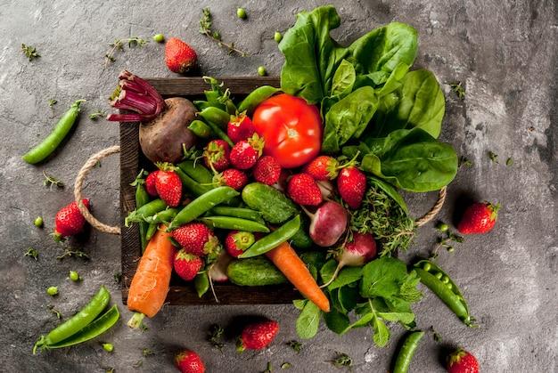 Рынок. здоровая веганская еда. свежие овощи, ягоды, зелень и фрукты в деревянном подносе: шпинат, мята, тимьян, клубника, морковь, свекла, огурцы, редька, зеленый горошек. на сером столе. вид сверху