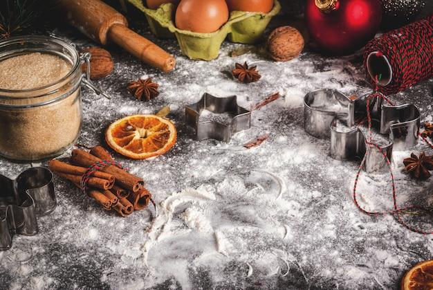 クリスマス、休日の料理。材料、スパイス、乾燥オレンジ、焼き型、クリスマスデコレーション(ボール、モミの木の枝、コーン)、黒い石のテーブル、