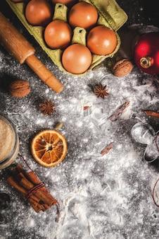 Рождество, праздничная кулинария. ингредиенты, специи, сушеные апельсины и формы для выпечки, рождественские украшения (шарики, еловая ветка, шишки), на черном каменном столе,