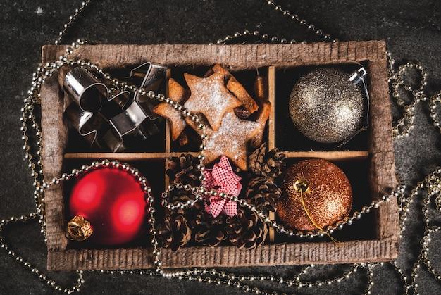 Рождество, праздничное оформление. елочные шары, гирлянда, пряничные звезды, печенье, формы, бантики для подарков, еловые шишки в деревянной коробке на черном каменном столе, вид сверху