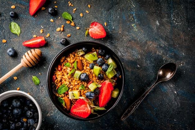 ミューズリーまたはグラノーラとナッツ、新鮮なベリー、フルーツストロベリー、ブルーベリー、キウイ、濃い青のテーブル、トップビューで健康的な朝食