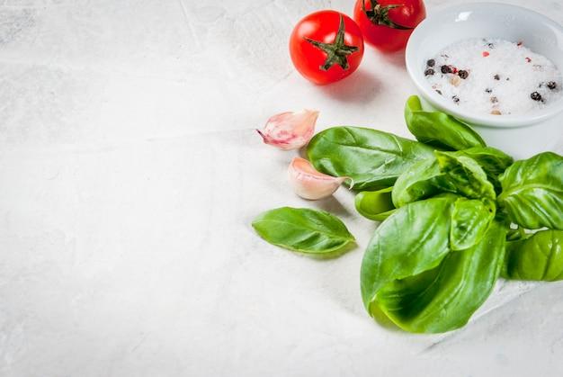 食品表面。ランチ、ランチを調理するための材料、野菜、スパイス。新鮮なバジルの葉、トマト、ニンニク、玉ねぎ、塩、コショウ。白い石のテーブルの上。コピースペース
