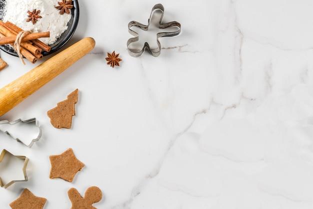 クリスマスのベーキング。ジンジャーブレッド、ジンジャーブレッド男性、星、クリスマスツリー、麺棒、スパイス(シナモンとアニス)、小麦粉のジンジャー生地。家庭の台所の白い大理石のテーブル。コピースペース